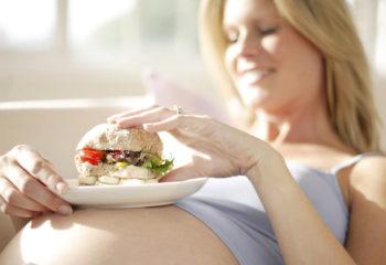 Pregnant woman eating a sandwich.